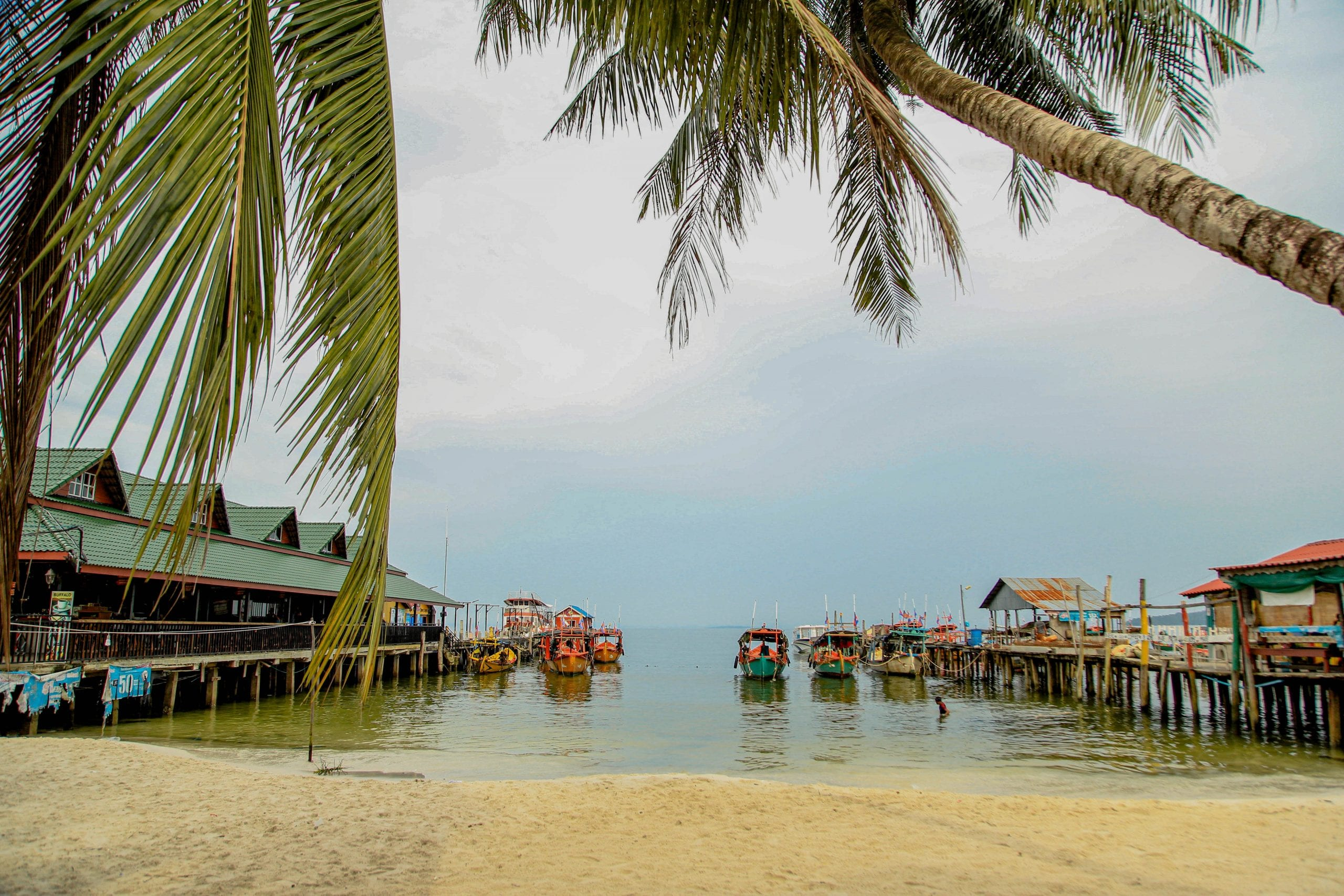 Beach, palm trees and boat on the ocean on Koh Rong, Cambodia