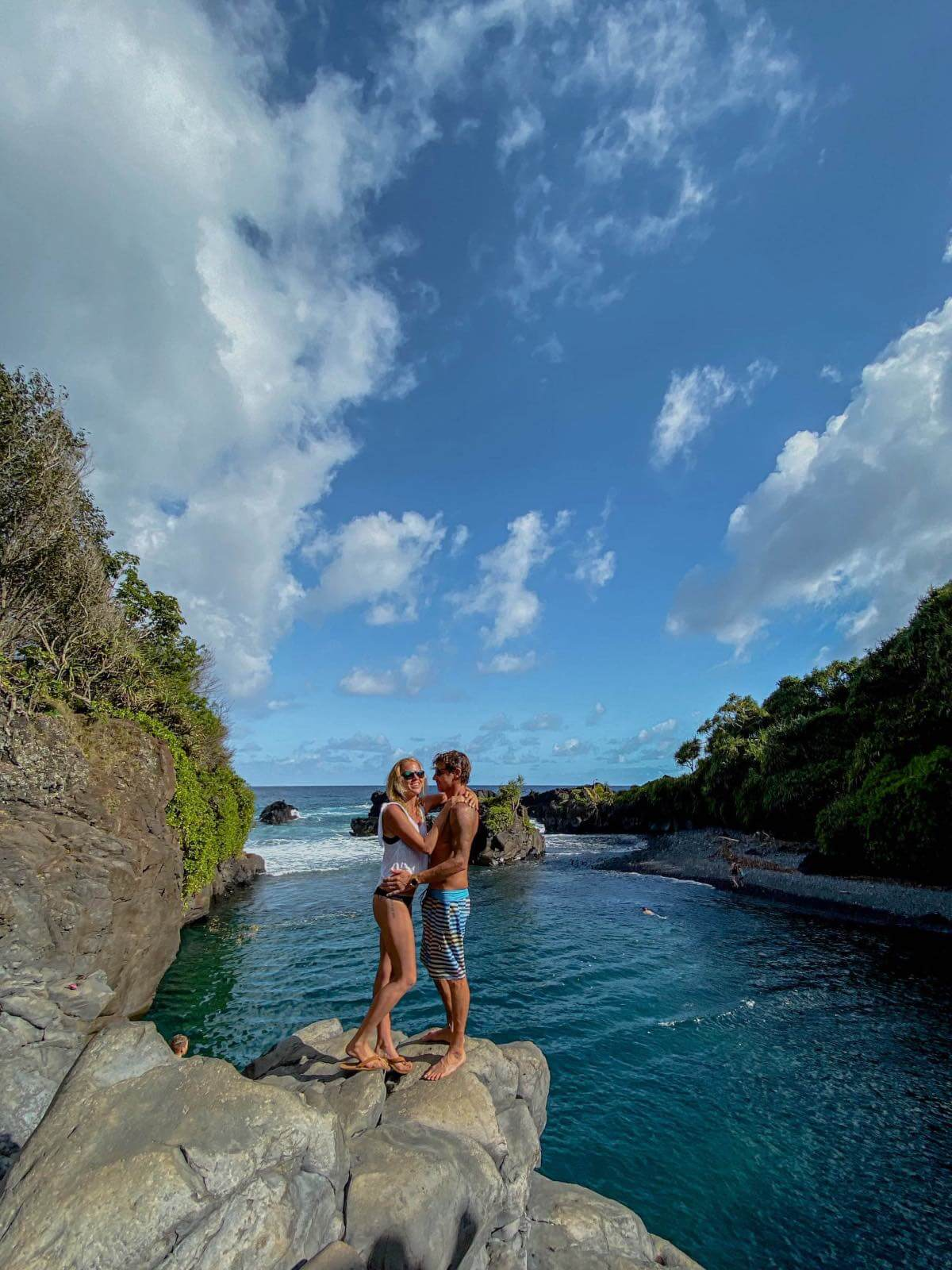 Jess and Joe on a cliff at Venus Pools in Hana HI