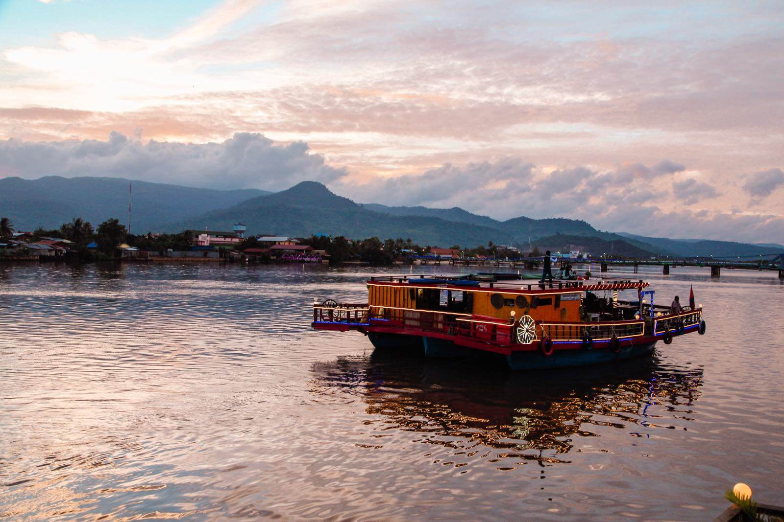 Boat floating on the Kampot river at sunset