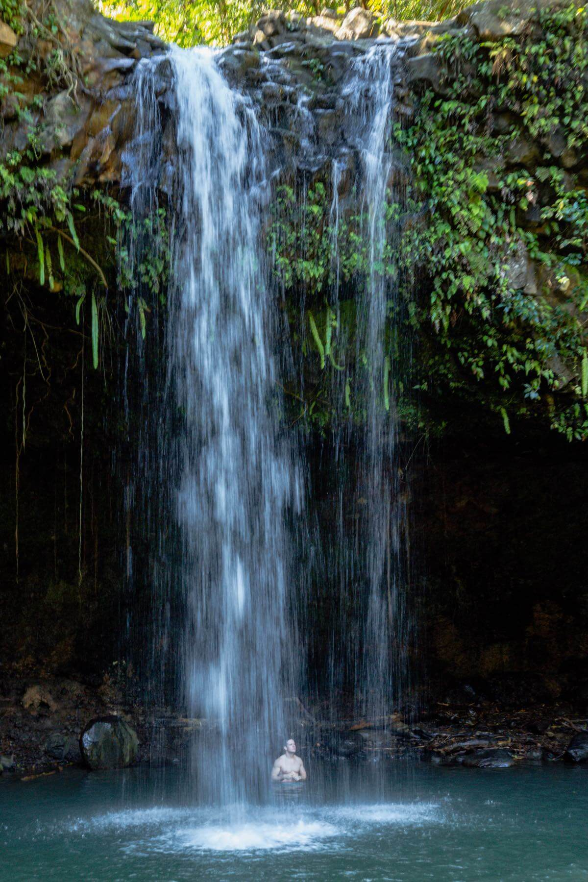 Guy under a waterfall at Twin Falls on Maui