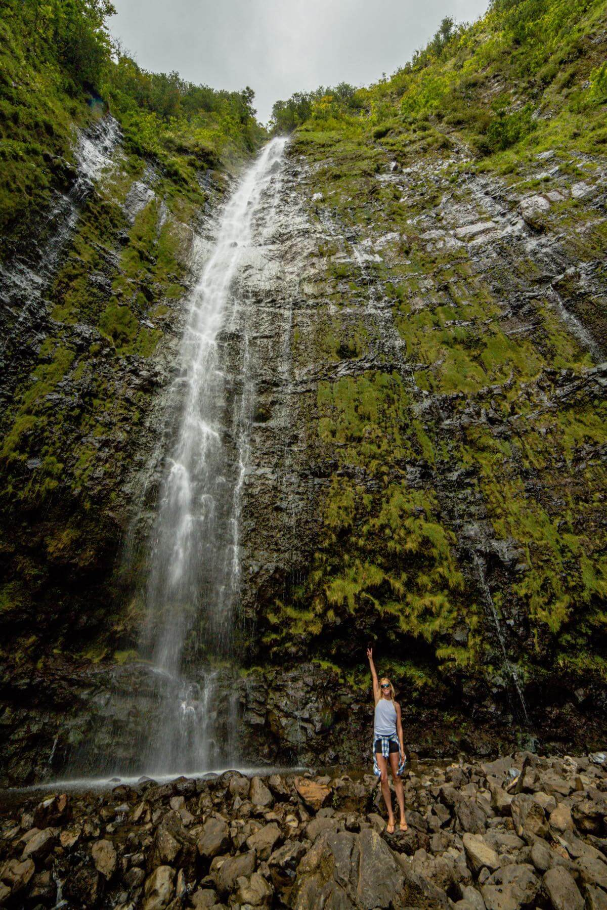 I'm Jess Traveling standing by Waimoku Falls on the Pipiwai Trail